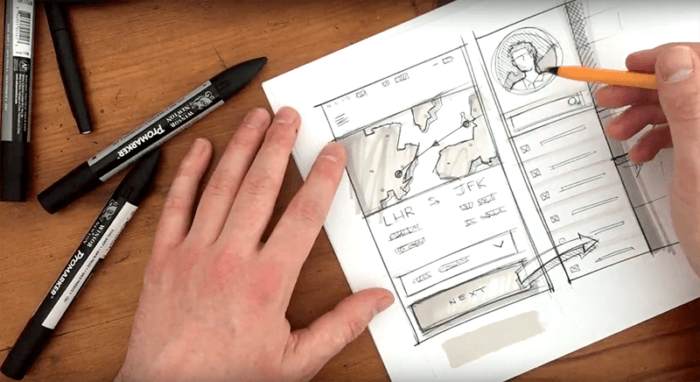 Designer sketching a website layout in a notebook