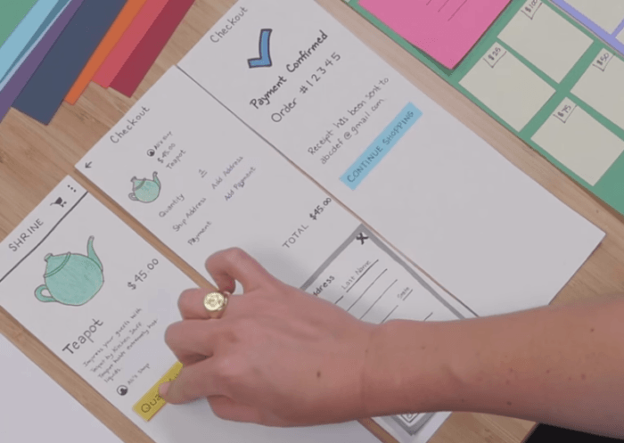 Person putting a paper prototype together on a table.
