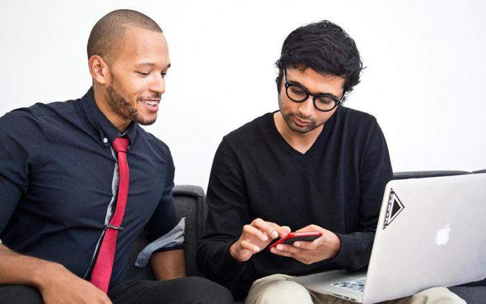 Two men sitting next to each other looking at a phone.