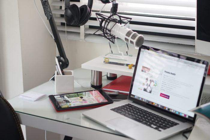 Photograph of a desk with a laptop on it and a professional grade microphone and headset