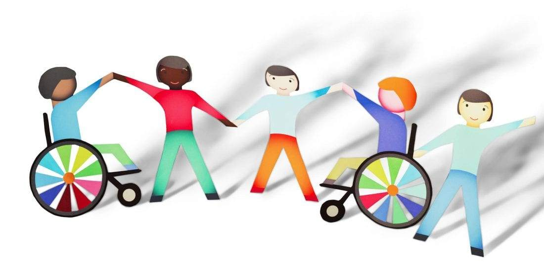 Image of people holding hands with some being in wheel chairs.