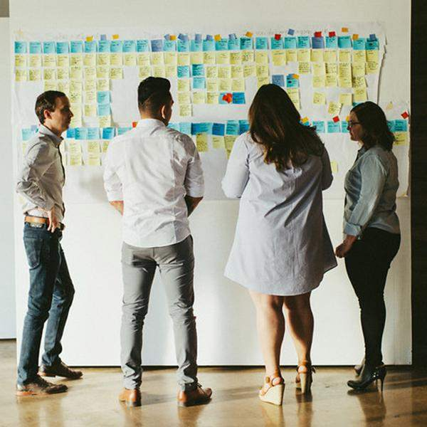 A cross-discipline team creating a redesign project roadmap that charts out each step in the project, and lets people map out areas of overlapping responsibility.