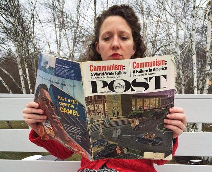 A photo of Christene Fair reading an old newspaper.
