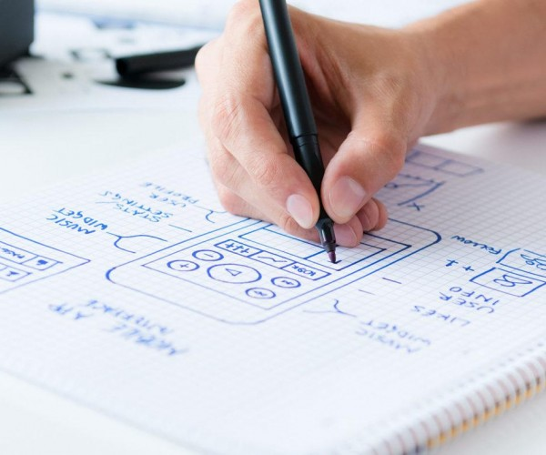 Designer develop a mobile application usability and drawing its framework on a paper.