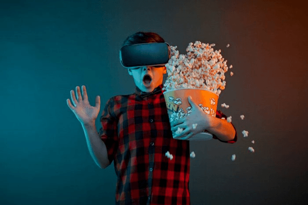 Boy getting scared and dropping popcorn while watching a movie using virtual reality