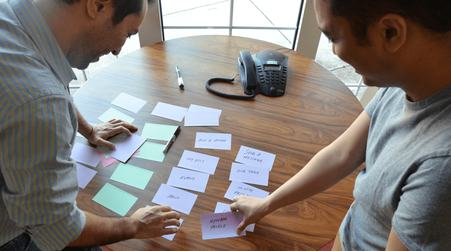 Two men using index cards doing a card sorting exercise on a table.