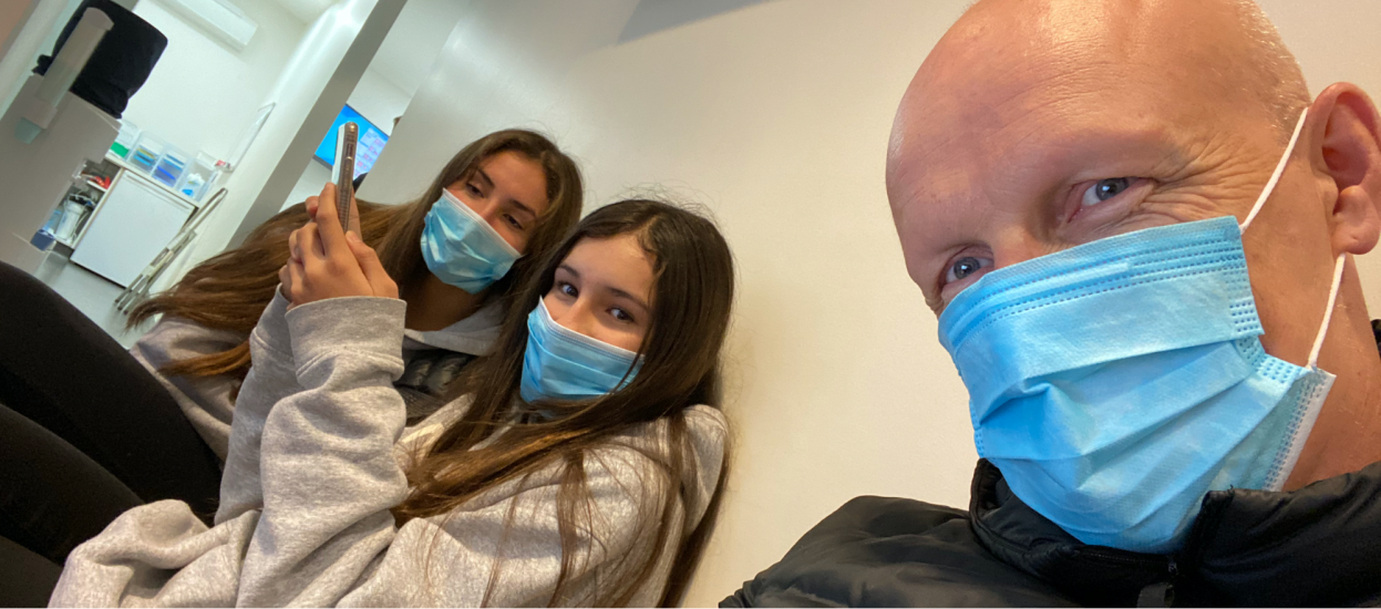 Guy Ligertwood and his daughters don face masks.