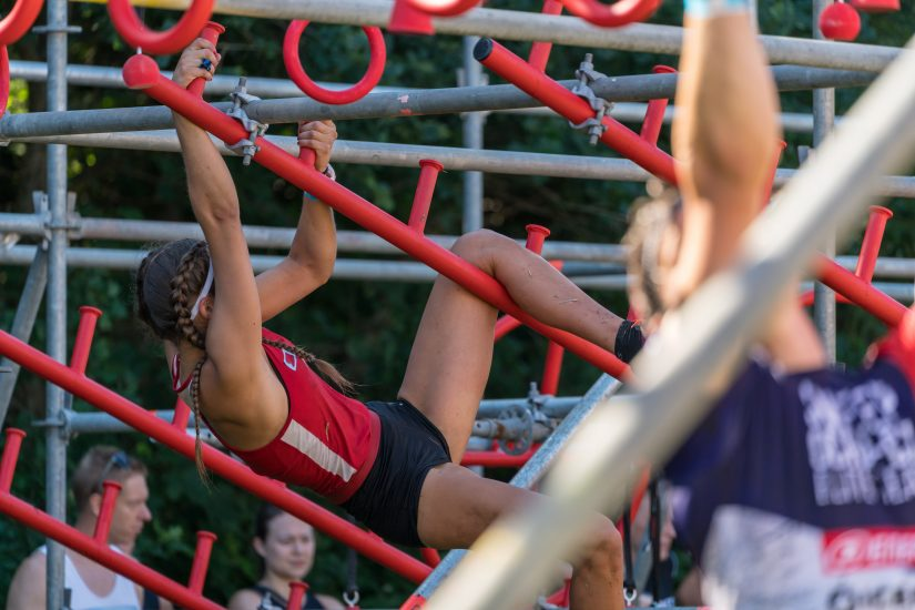 A woman, dressed in athletic gear, climbs a jungle gym as part of a competitive obstacle course. Other participants are visible in the foreground and background.
