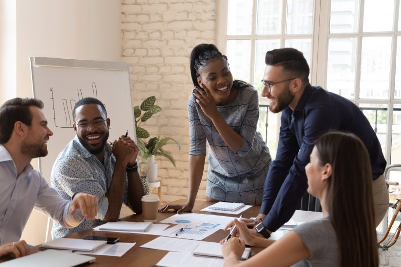 Happy friendly multiracial business team laughing working together at corporate briefing gathered at table, cheerful diverse office people group having fun talking enjoy teamwork during staff meeting