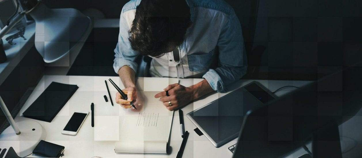 Man drawing on a sheet of paper at a desk in front of a computer